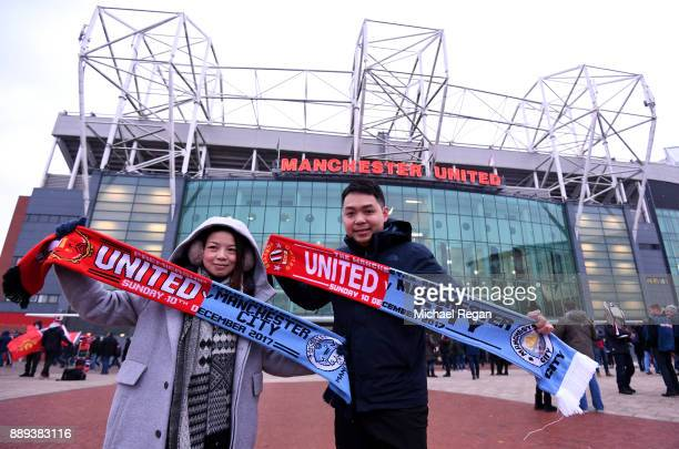 Fans pose outside the stadium prior to the Premier League match between Manchester United and Manchester City at Old Trafford on December 10 2017 in...