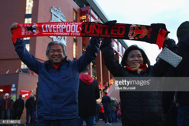 Fans pose with a scarf outside the stadium before the Premier League match between Liverpool and Manchester United at Anfield on October 17 2016 in...