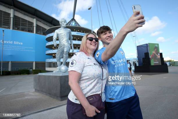 Fans pose with a statue of David Silva of Manchester City that is seen outside the stadium prior to the Premier League match between Manchester City...