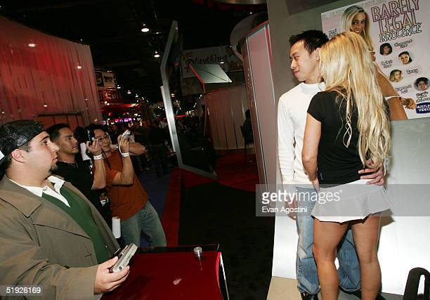 Fans pose with model Austyn Moore the 2005 AVN Adult Entertainment Expo at the Sands Convention Center at the Venetian Hotel January 7 2005 in Las...