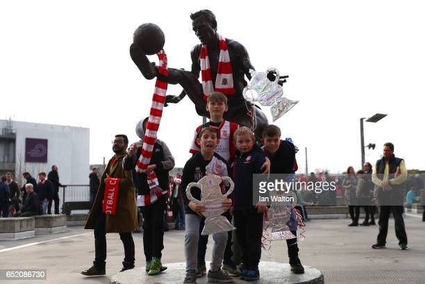 Fans pose with the Dennis Bergkamp statue outside the stadium prior to The Emirates FA Cup QuarterFinal match between Arsenal and Lincoln City at...