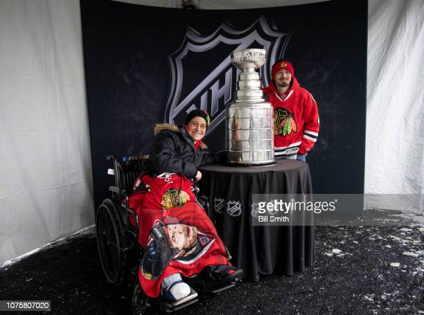 Fans pose with the Stanley Cup during the Bridgestone NHL Winter Classic Park fan festival at Millenium Park on December 29 2018 in Chicago Illinois