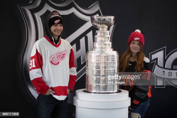 Fans pose with the Stanley Cup during the NHL Centennial Fan Arena Truck Tour stop on Cass Avenue on December 3 2017 in Detroit Michigan