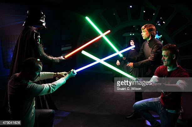 Fans pose with Wax figures of Star Wars characters Luke Sykwalker and Darth Vader at 'Star Wars At Madame Tussauds' on May 12 2015 in London England