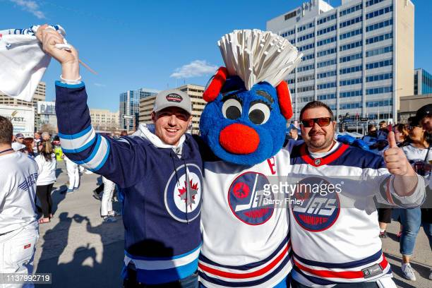 Fans pose with Winnipeg Jets Heritage Mascot Benny during the Whiteout Street Party prior to NHL action between the Jets and the St Louis Blues in...