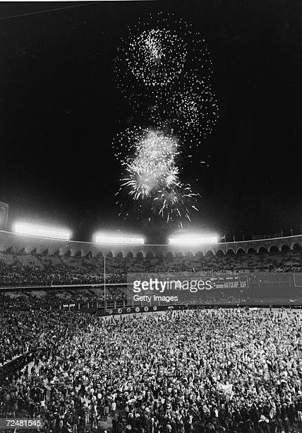 Fans pour onto the field at Busch Stadium at the conclusion of the World Series as fireworks blast overhead St Louis Missouri October 20 1982 St...