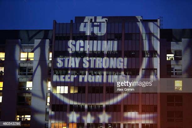 Fans project a message reading '45 Schumi Stay strong Keep fighting' on a wall of the Grenoble University Hospital Centre where former German Formula...