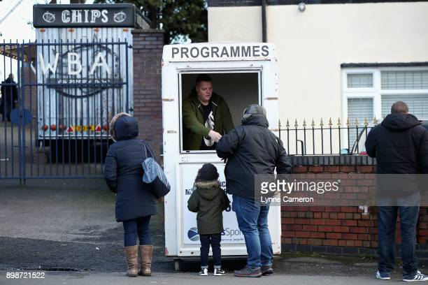 Fans purchase match day programmes prior to the Premier League match between West Bromwich Albion and Everton at The Hawthorns on December 26 2017 in...