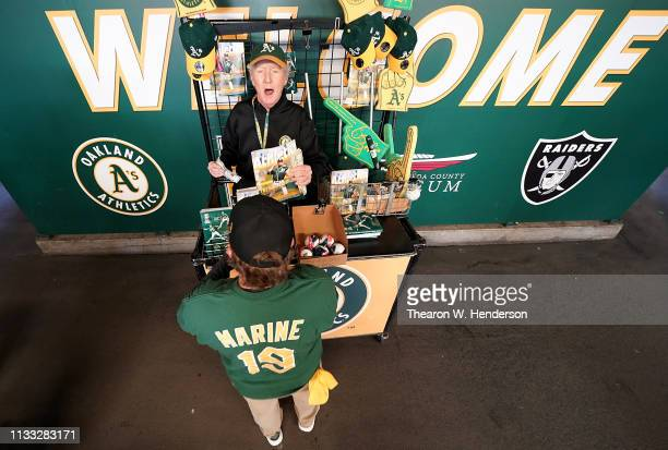 Fans purchase programs from a vendor on Opening Day prior to the start of a Major League Baseball game between the Los Angeles Angels of Anaheim and...