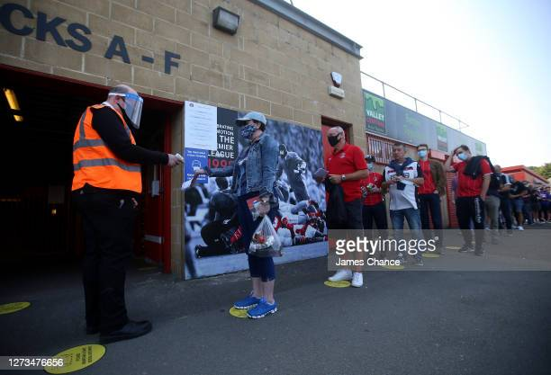 Fans que socially distanced on markers on the ground as they enter the stadium ahead of the Sky Bet League One match between Charlton Athletic and...