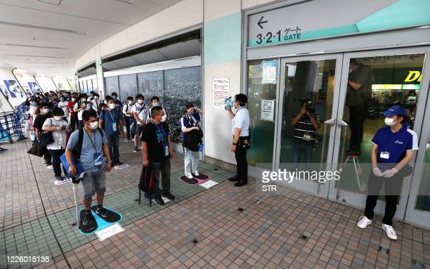 Fans queue with social distancing to enter the Nagoya Dome to watch the Japanese professional baseball match between Chunichi and Hiroshima in Nagoya...
