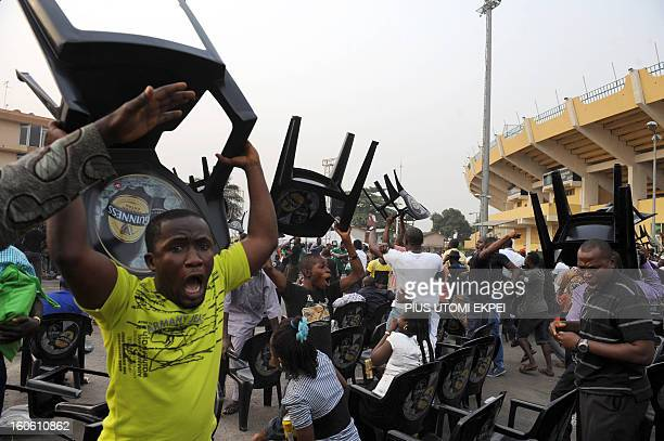 Fans raise chairs to celebrate Nigeria football team's victory over Ivory Coast to advance into the semi final of the 2013 African Cup of Nations on...