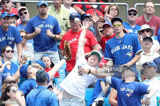 TORONTO ON JULY 2 Fans reach for a ball as the Toronto Blue Jays beat the Cleveland Indians 96 to end their 14 game winning streak at the Rogers...