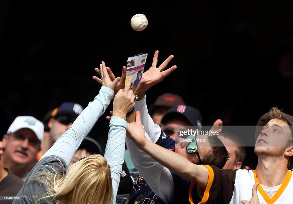 Fans reach for a fly ball during a game between the Atlanta Braves and the San Diego Padres at Petco Park on April 15, 2010 in San Diego, California.