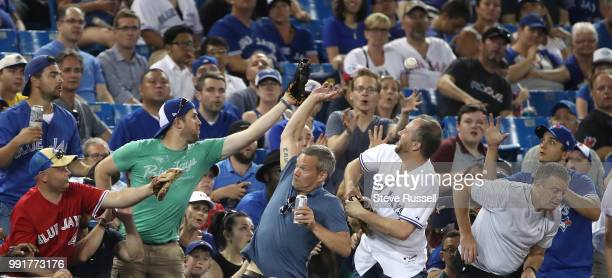 TORONTO ON JULY 4 Fans reach for a foul ball as the Toronto Blue Jays fall to the New York Mets 63 at the Rogers Centre in Toronto July 4 2018