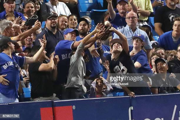 TORONTO ON AUGUST 10 Fans reach for a foul ball as the Toronto Blue Jays shutout the New York Yankees 40 at the Rogers Centre in Toronto August 10...