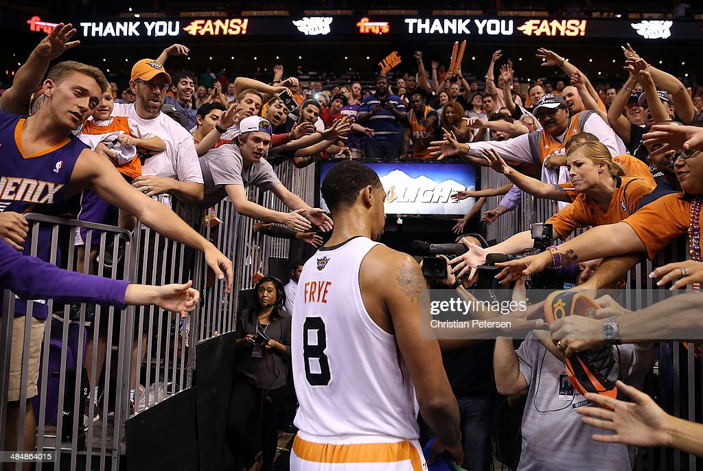 Fans reach for Channing Frye #8 of the Phoenix Suns as he walks off the court following the NBA game against the Memphis Grizzlies at US Airways Center on April 14, 2014 in Phoenix, Arizona. The Grizzlies defeated the 97-91.