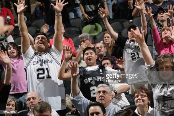 Fans reach for tee-shirts, tossed by cheerleaders, during the NBA game between the San Antonio Spurs and the Denver Nuggets on February 20, 2007 at...