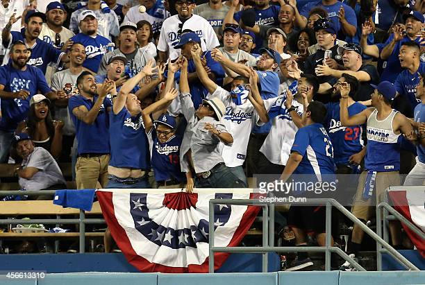 Fans reach for the ball on a two run homerun hit by Adrian Gonzalez of the Los Angeles Dodgers in the eighth inning of Game One of the National...