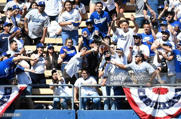 Fans reach for the home run ball hit by Austin Barnes of the Los Angeles Dodgers during the fourth inning against Arizona Diamondbacks on Opening Day...