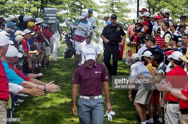 Fans reach out to shake hands with US golfers Tiger Woods and Australian golfer Jason Day as they depart the green during the second round of the...