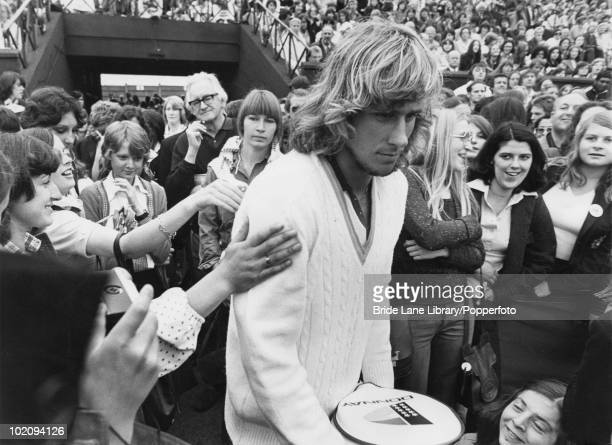 Fans reach out to touch Swedish tennis player Bjorn Borg prior to the start of his competition to reach the quarterfinals of the Men's Singles...