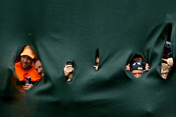 Fans reach to watch Tiger Woods putt on the 18th hole during the final...