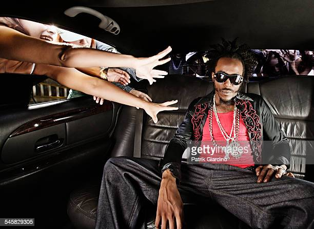 fans reaching for man in limo - pimped car stock photos and pictures