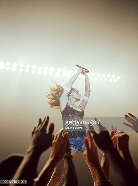 fans reaching towards singer performing on stage, (focus on singer) - mesh shirt stock photos and pictures