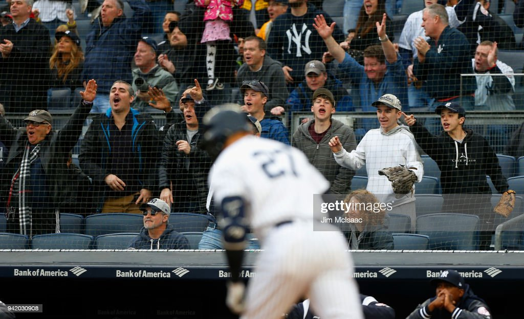 Fans react after Giancarlo Stanton #27 of the New York Yankees hit a first inning two run home run against the Tampa Bay Rays at Yankee Stadium on April 4, 2018 in the Bronx borough of New York City.
