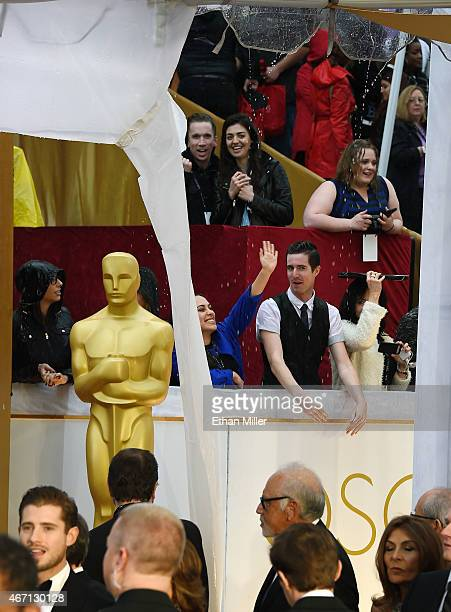 Fans react as it rains on them while they watch celebrities arrive at the 87th Annual Academy Awards at Hollywood Highland Center on February 22 2015...