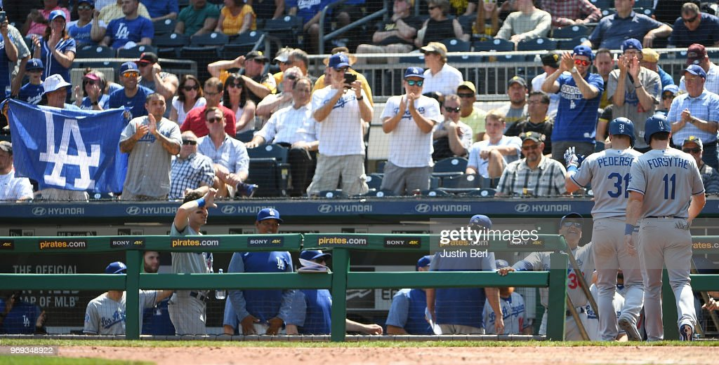 Fans react as Joc Pederson #31 of the Los Angeles Dodgers is greeted by teammates in the dugout after hitting a two run home run in the eighth inning during the game against the Pittsburgh Pirates at PNC Park on June 7, 2018 in Pittsburgh, Pennsylvania.