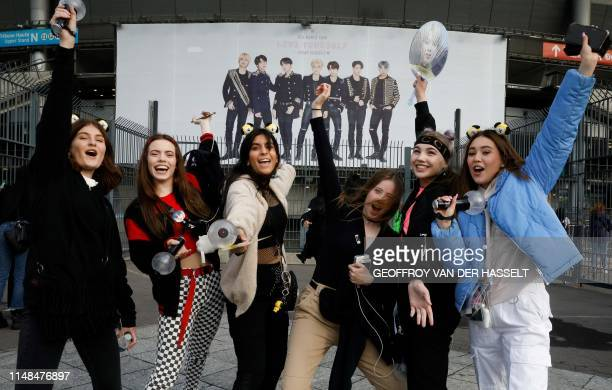 Fans react as they arrive for a concert of the South Korean K-pop boy band BTS at the Stade-de-France stadium in Saint-Denis, on the outskirts of...