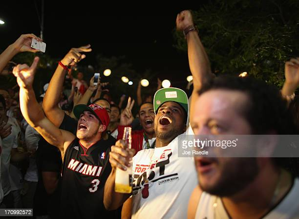 Fans react as they watch on television the Miami Heat win the NBA title against the San Antonio Spurs June 20 2013 in Miami Florida The Heat won back...