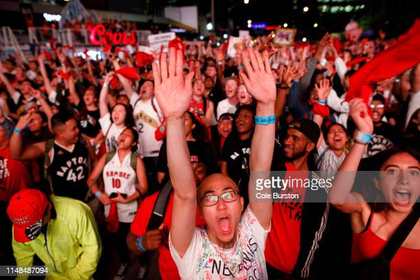 Fans react as Toronto Raptors fans gather to watch Game 4 of the NBA Finals series outside Scotiabank Arena at 'Jurassic Park' on June 7 2019 in...