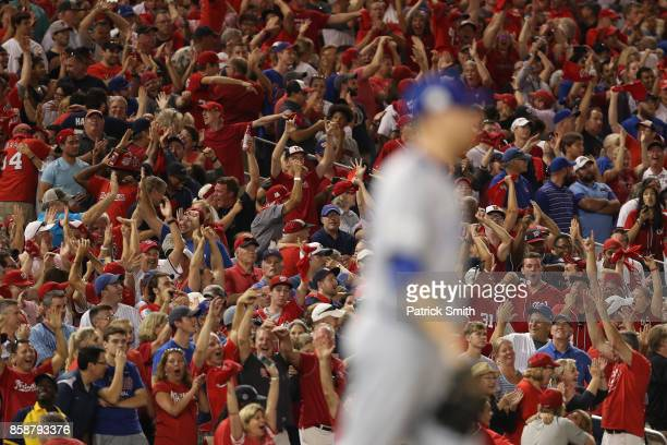 Fans react to a three run Bryce Harper of the Washington Nationals home run against the Chicago Cubs in the eighth inning during game two of the...