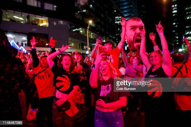 Fans react to a Toronto Raptors win as Raptors fans gather to watch Game 4 of the NBA Finals series outside Scotiabank Arena at 'Jurassic Park' on...