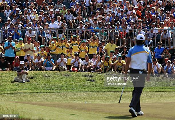 Fans react to Jason Day of the International Team putting on the 18th hole during the Day Two Four-Ball Matches of the 2011 Presidents Cup at Royal...