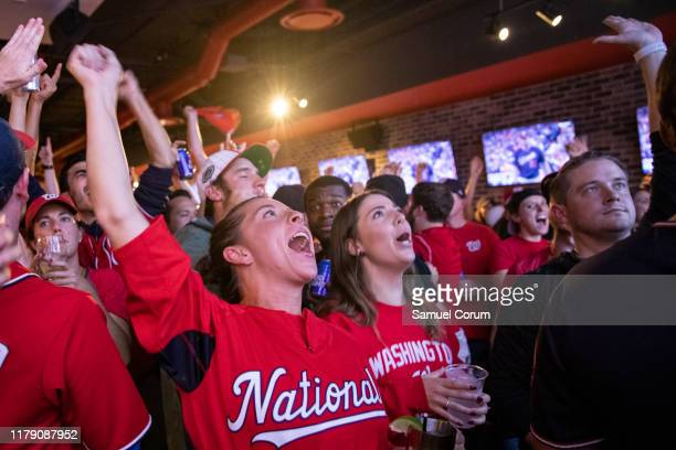 Fans react to the World Series Game 7 on a big screen just a block from Nationals Park at Walter's Sports Bar on October 30 2019 in Washington DC The...