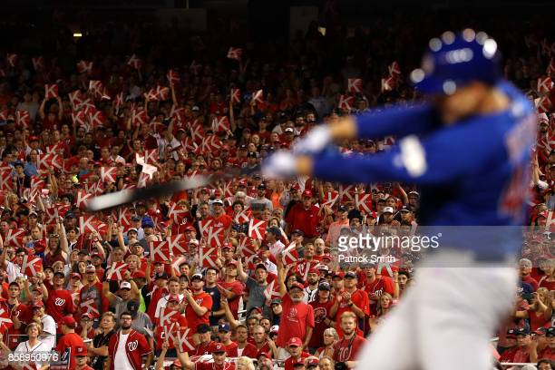 Fans react with 'K' strikeout signs as Anthony Rizzo of the Chicago Cubs swings during the fourth inning against the Washington Nationals in game one...