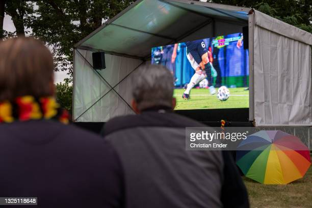 Fans reacting outside in a beer garden while an umbrella in LGBT rainbow colors stands next to the screen on June 23, 2021 in Berlin, Germany....