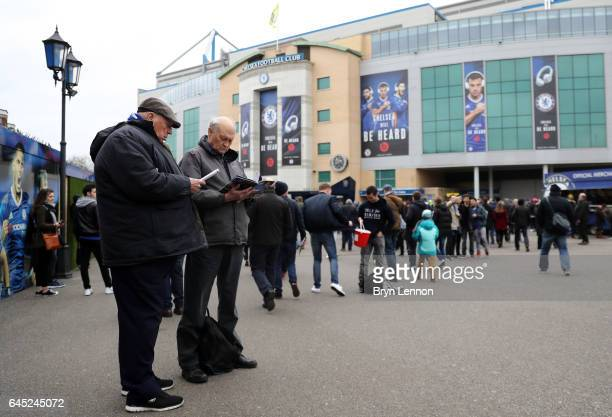 Fans read the match day programme outside the stadium prior to the Premier League match between Chelsea and Swansea City at Stamford Bridge on...