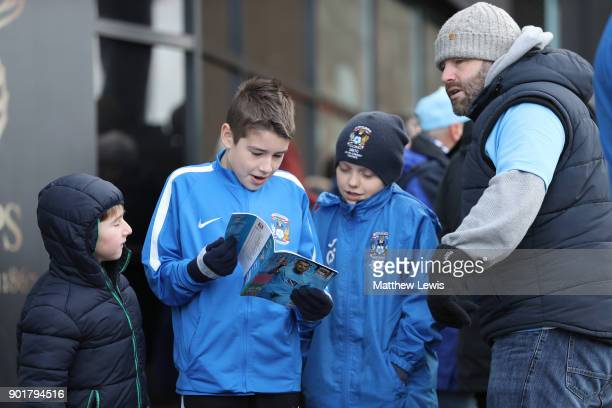 Fans read the matchday programme prior to The Emirates FA Cup Third Round match between Coventry City and Stoke City at Ricoh Arena on January 6 2018...
