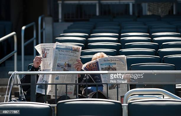 Fans reading the the New York Times and the Wall Street Journal before the game between the Washington Nationals and the New York Mets at Citi Field...