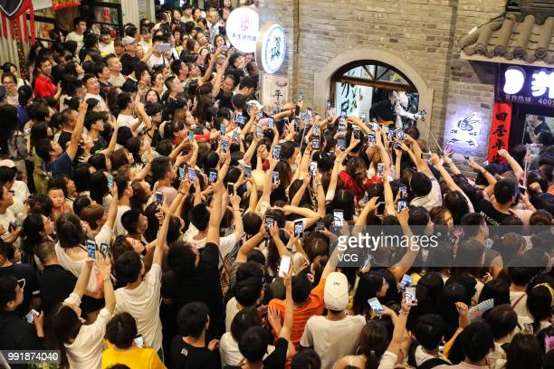 Fans record videos on their smartphones as boy band Modern Brothers performs during a live webcast at Andong Old Street on June 30, 2018 in Dandong,...