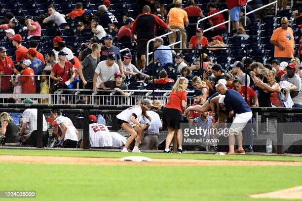 Fans run for cover after what was believed to be shots were heard during a baseball game between the San Diego Padres the Washington Nationals at...