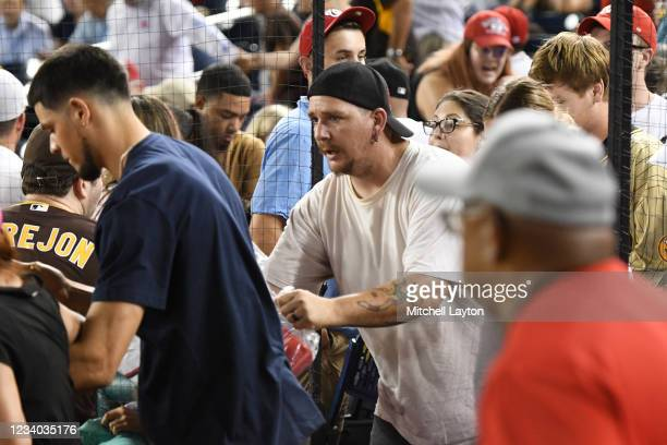 Fans run onto the field for cover after shots are heard from a shooting outside the stadium that sent players and fans seeking shelter during a...