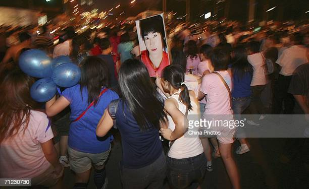 Fans rush to the car carrying Korean singing group Super Junior as they arrive at the opening ceremony of 9th Shanghai International Film Festival on...