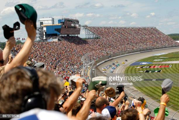 Fans salute to the cars before the Monster Energy NASCAR Cup Series FireKeepers Casino 400 at Michigan International Speedway on June 18 2017 in...
