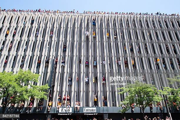 Fans scale the side of a parking garage to get a better view during the Cleveland Cavaliers 2016 championship victory parade and rally on June 22...